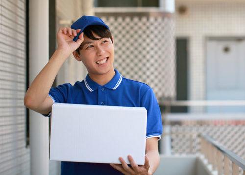 白い箱を持つ青い帽子とポロシャツの男性